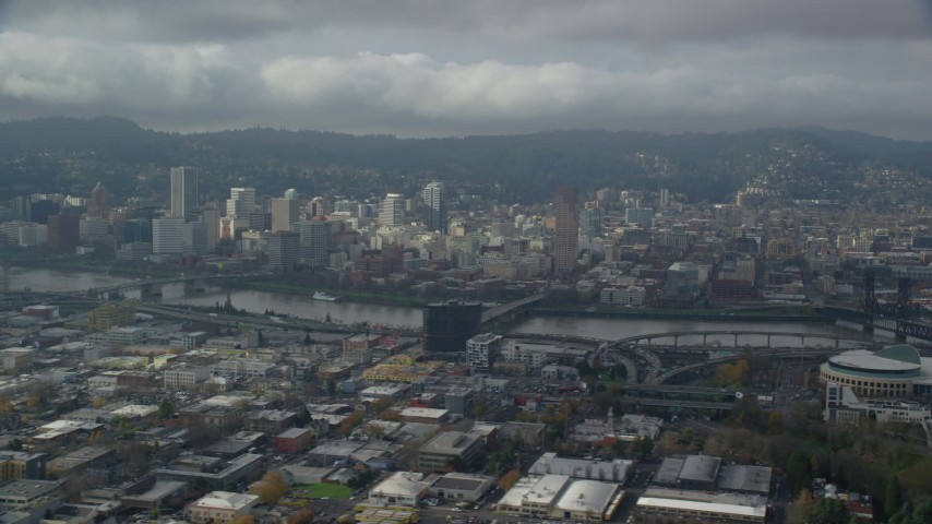 6K stock footage aerial video flying over office buildings and high-rises with view of Downtown Portland with clouds, Oregon Aerial Stock Footage | AX153_023