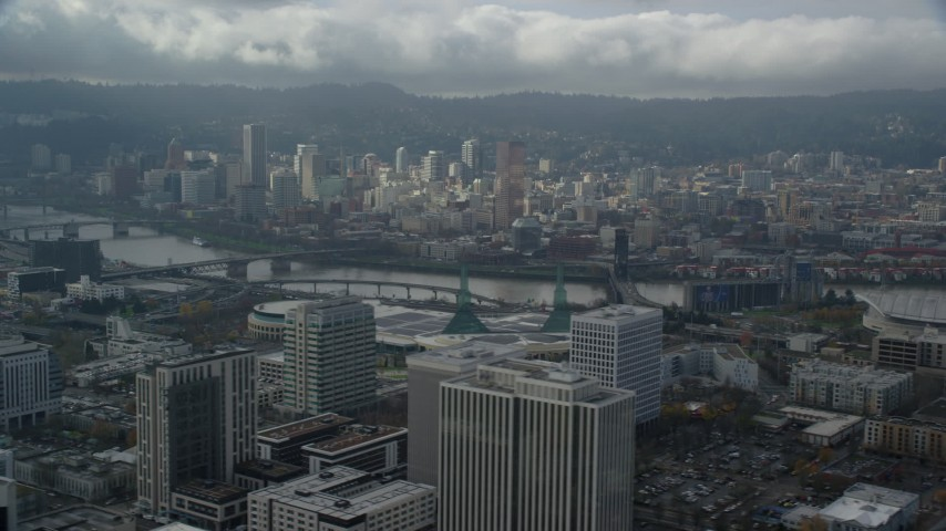 6K stock footage aerial video flying by high-rises and convention center looking toward Moda Center and Downtown Portland, Oregon Aerial Stock Footage | AX153_024