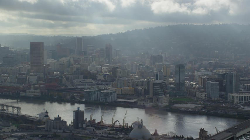 Fly along Willamette River looking toward Downtown Portland, Oregon Aerial Stock Footage | AX153_027