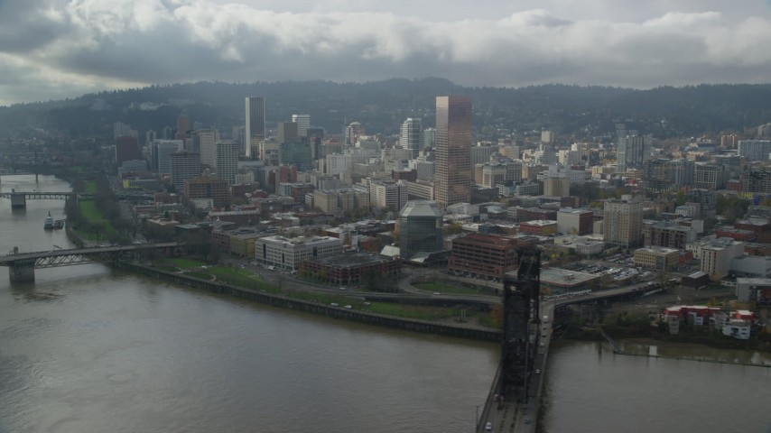 6K stock footage aerial video flying over Willamette River with views of skyscrapers and high-rises, Downtown Portland, Oregon Aerial Stock Footage | AX153_032