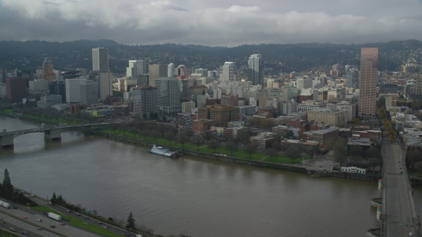 6K stock footage aerial video flying by skyscrapers and high-rises with river in foreground, Downtown Portland, Oregon Aerial Stock Footage | AX153_033