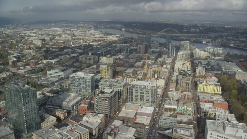 6K stock footage aerial video flying over city buildings toward the river and Fremont Bridge, Downtown Portland, Oregon Aerial Stock Footage | AX153_040