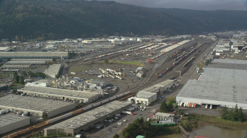 6K stock footage aerial video passing a train yard, Northwest Portland, Oregon Aerial Stock Footage | AX153_060