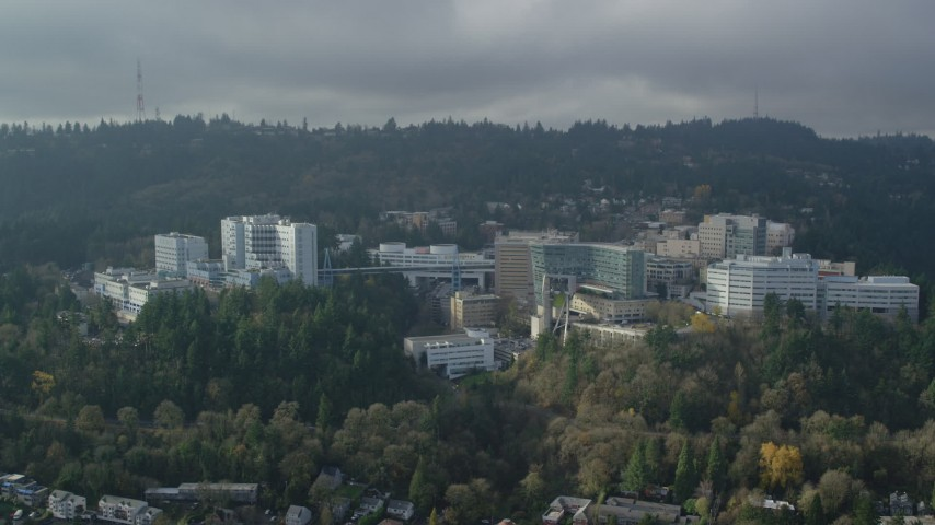 6K aerial video of a reverse view of the Oregon Health and Science University in Portland, Oregon Aerial Stock Footage AX153_082