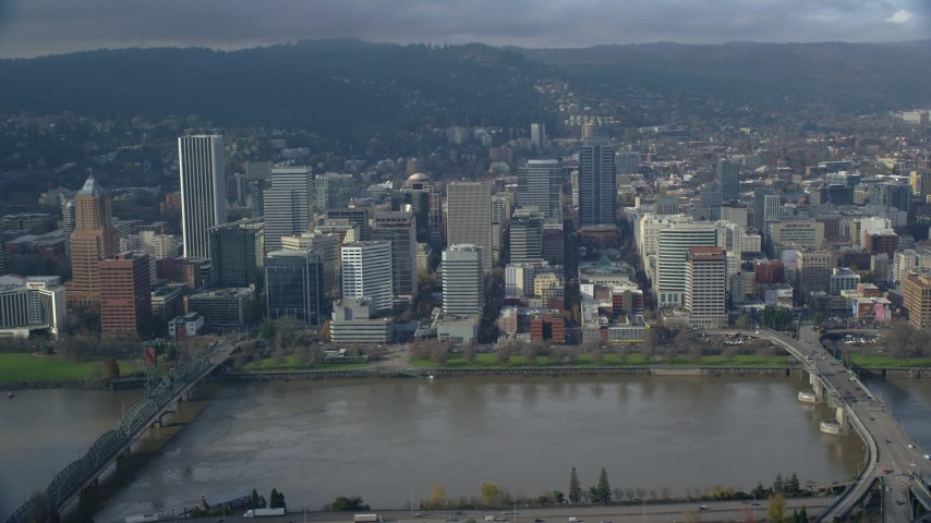 6K stock footage aerial video of skyscrapers and Morrison Bridge seen from across the Willamette River, Downtown Portland, Oregon Aerial Stock Footage | AX153_121