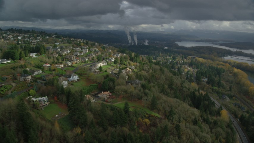 6K stock footage aerial video flying over Highway 14 by suburban homes to approach paper mill in Camas, Washington Aerial Stock Footage | AX153_148