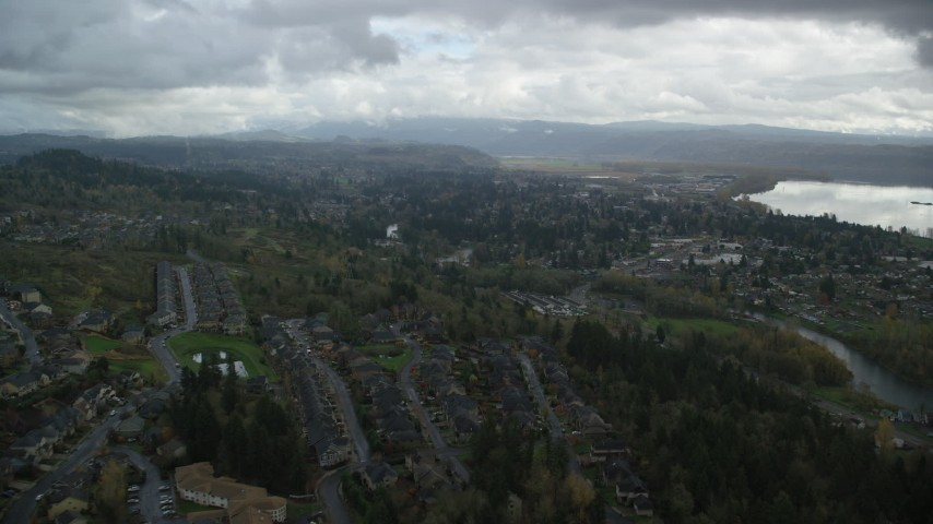 6K stock footage aerial video flying over Camas to approach tract homes and the Washougal River in Washougal, Washington Aerial Stock Footage | AX153_159