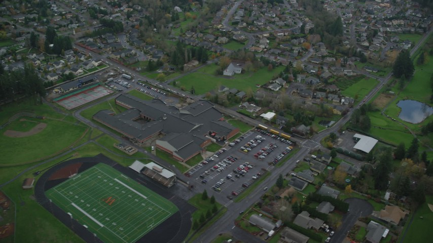 6K stock footage aerial video of a bird's eye view of Washougal High School, suburban homes, and Orchard Hills Golf Club in Washougal, Washington Aerial Stock Footage | AX153_171