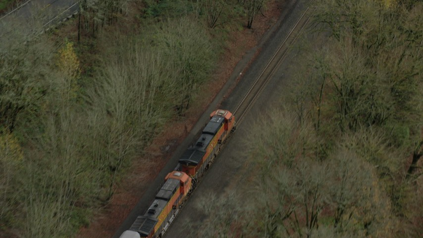 6K stock footage aerial video of a bird's eye tracking a train engine traveling through Columbia River Gorge, Oregon Aerial Stock Footage   AX153_182