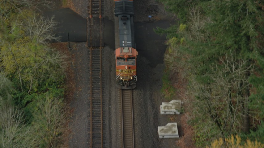 6K stock footage aerial video of a reverse view tracking a train in Columbia River Gorge, reveal trucks on country road in Oregon Aerial Stock Footage | AX153_183