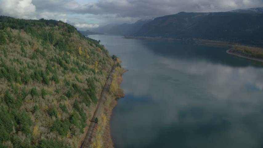 6K stock footage aerial video of train tracks at the bottom of a cliff in Columbia River Gorge, Oregon Aerial Stock Footage | AX154_001