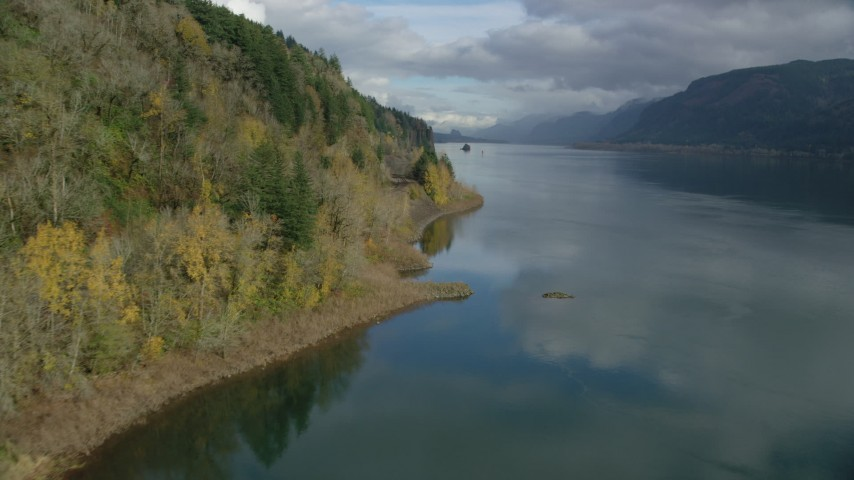 6K stock footage aerial video flying over the river and follow train tracks by the cliffs in Columbia River Gorge, Oregon Aerial Stock Footage | AX154_003