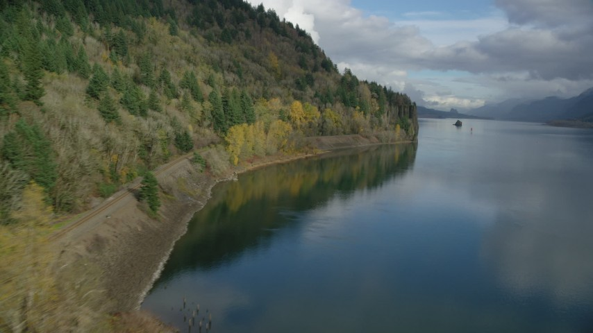 6K stock footage aerial video flying low over the water to approach train tracks in the Columbia River Gorge, Oregon Aerial Stock Footage | AX154_004