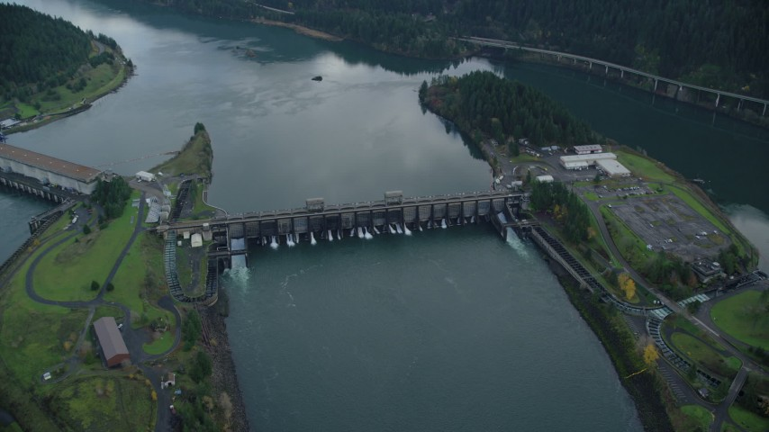 6K stock footage aerial video tilting to a bird's eye view of Bonneville Dam in Columbia River Gorge and fly over Aerial Stock Footage | AX154_040
