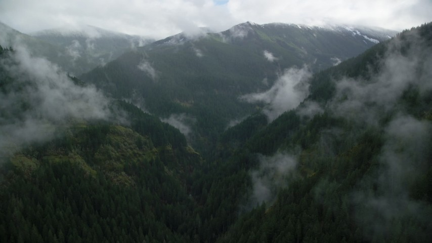 6K stock footage aerial video flying through a misty canyon to approach a mountain ridge with snow in Cascade Range, Hood River County, Oregon Aerial Stock Footage | AX154_052