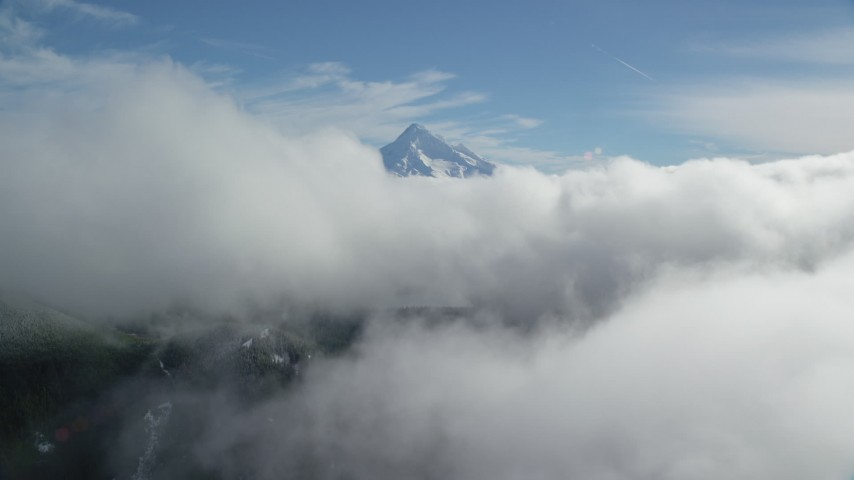 6K aerial video approaching Mount Hood, visible above a layer of thick clouds, Cascade Range, Oregon Aerial Stock Footage | AX154_060