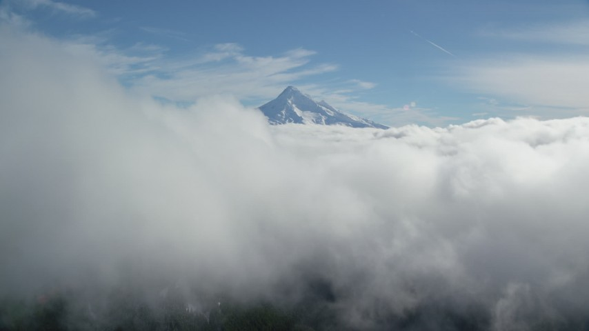 6K aerial video flying over thick clouds toward the summit of Mount Hood, Cascade Range, Oregon Aerial Stock Footage | AX154_061