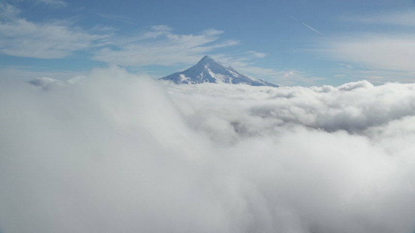 6K aerial video flying over thick cloud layer to approach snowy Mount Hood, Cascade Range, Oregon Aerial Stock Footage AX154_062