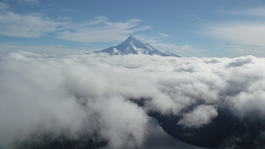 Flying above clouds to approach snowy Mount Hood, Cascade Range, Oregon Aerial Stock Footage | AX154_063
