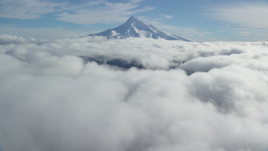 6K stock footage aerial video approaching snowy summit while flying over clouds, Mount Hood, Cascade Range, Oregon Aerial Stock Footage AX154_066 | Axiom Images