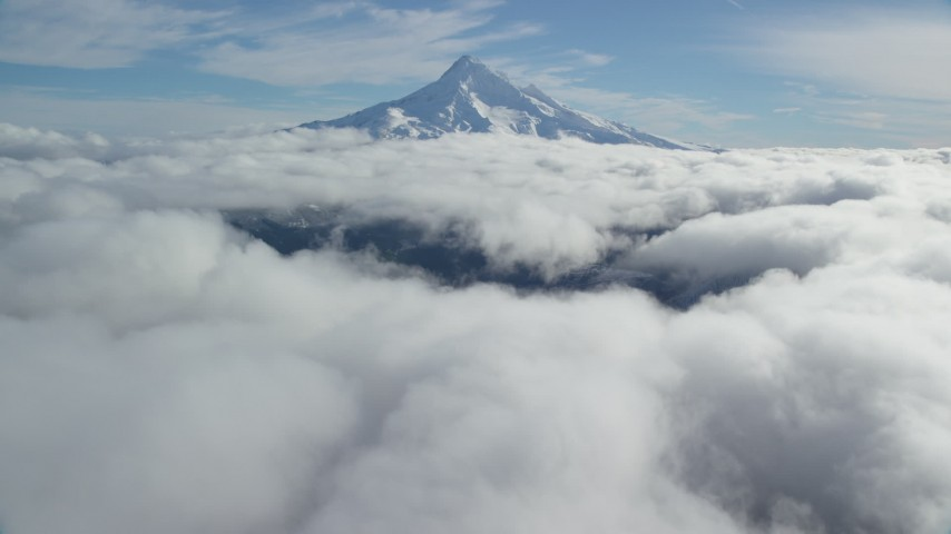 Approach Mount Hood summit with snow and fly over clouds, Mount Hood, Cascade Range, Oregon Aerial Stock Footage AX154_067