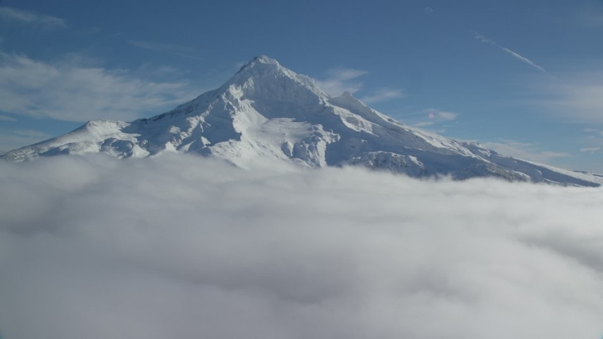 6K aerial video of a slow approach to snowy Mount Hood, surrounded by clouds, Mount Hood, Cascade Range, Oregon Aerial Stock Footage | AX154_075