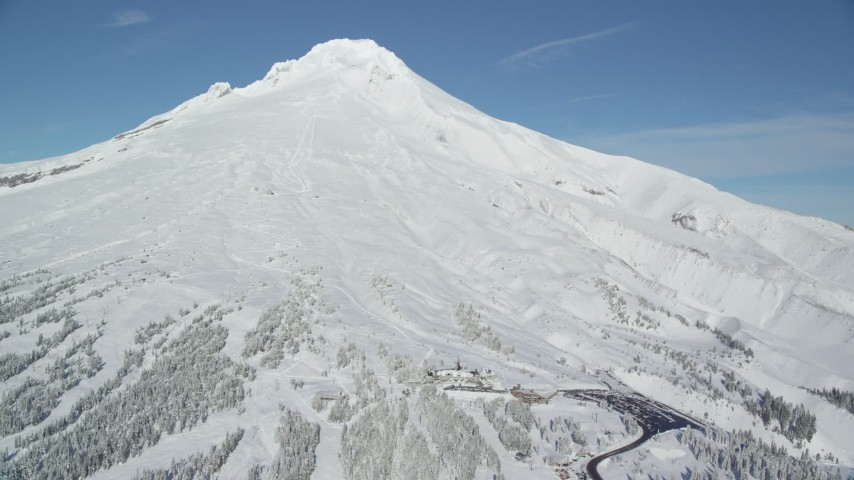 6K aerial video orbiting steep mountain slopes with snow and Timberline Lodge, Mount Hood, Cascade Range, Oregon Aerial Stock Footage | AX154_090