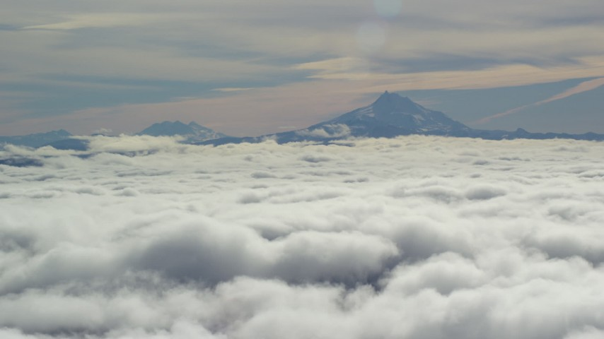 6K stock footage aerial video of Mount Jefferson and the Three Sisters Volcanoes seen from across low clouds, Cascade Range, Oregon Aerial Stock Footage | AX154_098