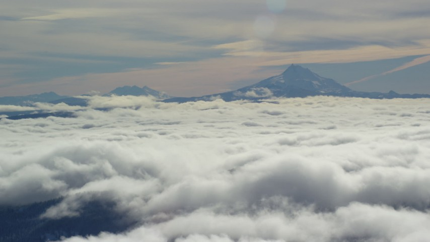 6K aerial video of Mount Jefferson and Three Sisters Volcanoes, seen above the clouds, Cascade Range, Oregon Aerial Stock Footage | AX154_099