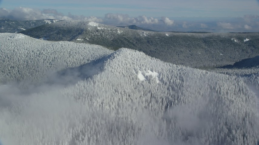 6K stock footage aerial video approaching a snow covered mountain ridge and forest in the Cascade Range, Oregon Aerial Stock Footage | AX154_100
