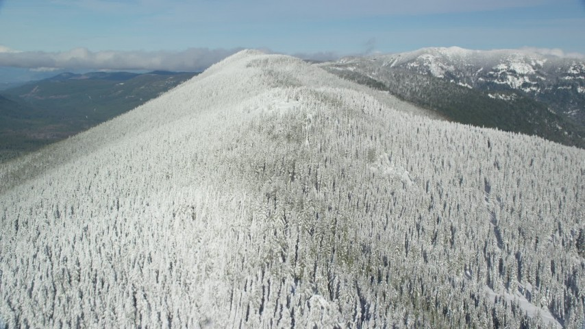 6K stock footage aerial video flying over frozen forest on a mountain ridge, Cascade Range, Oregon Aerial Stock Footage | AX154_103