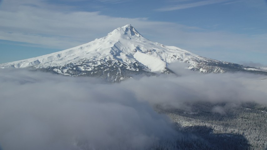 6K aerial video of a snow-capped mountain peak and low clouds, Mount Hood, Cascade Range, Oregon Aerial Stock Footage | AX154_117