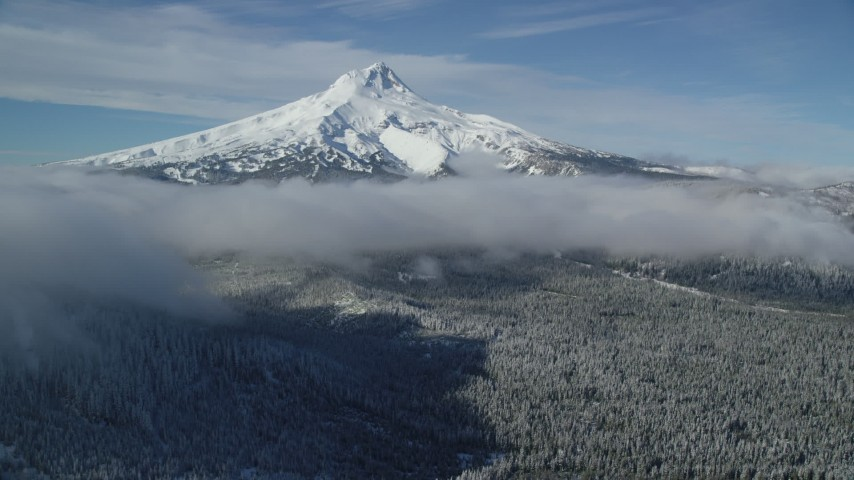 6K stock footage aerial video of snowy mountain peak with low clouds over forest, Mount Hood, Cascade Range, Oregon Aerial Stock Footage | AX154_118