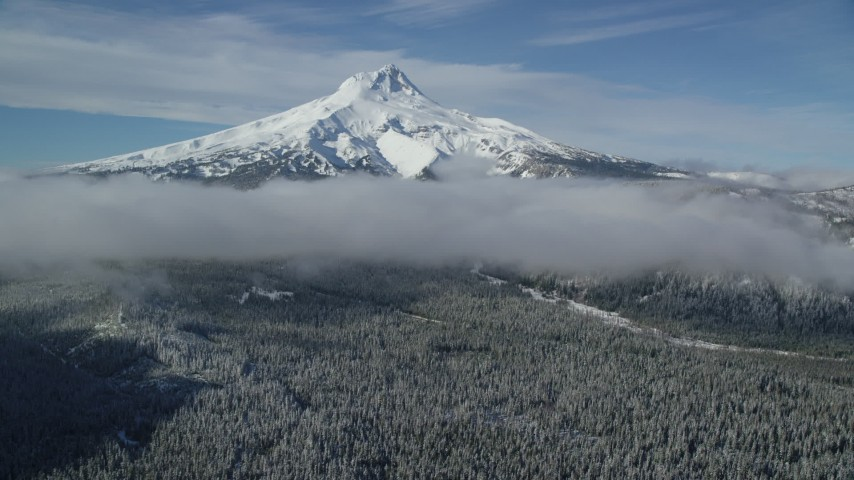 6K aerial video of snow-capped peak and low clouds over forest, Mount Hood, Cascade Range, Oregon Aerial Stock Footage | AX154_119