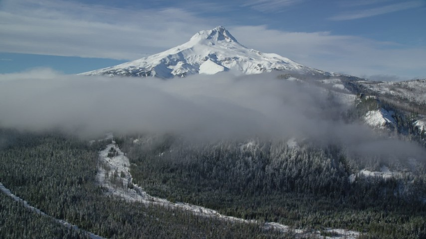 6K aerial video of low clouds over forest and ridge near snow-capped Mount Hood, Cascade Range, Oregon Aerial Stock Footage | AX154_121