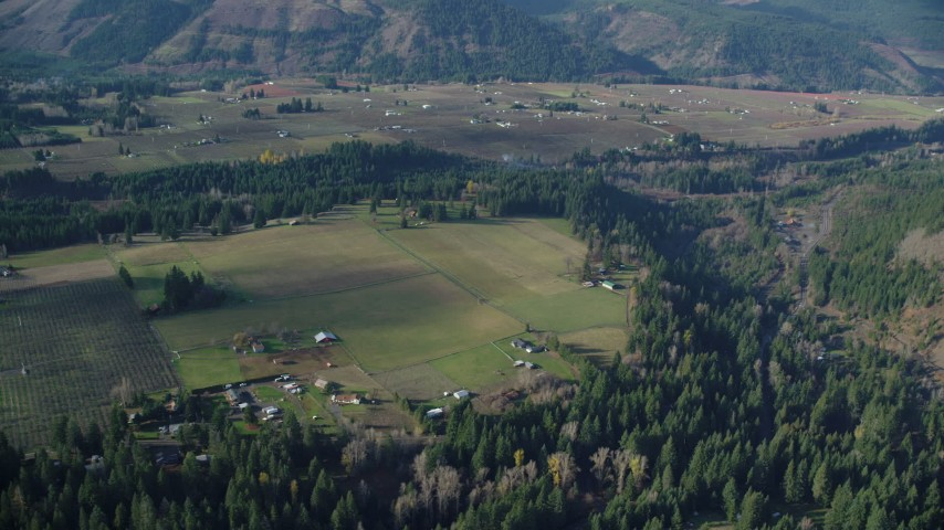 6K stock footage aerial video passing rural farms and fields in Parkdale, Oregon Aerial Stock Footage | AX154_144