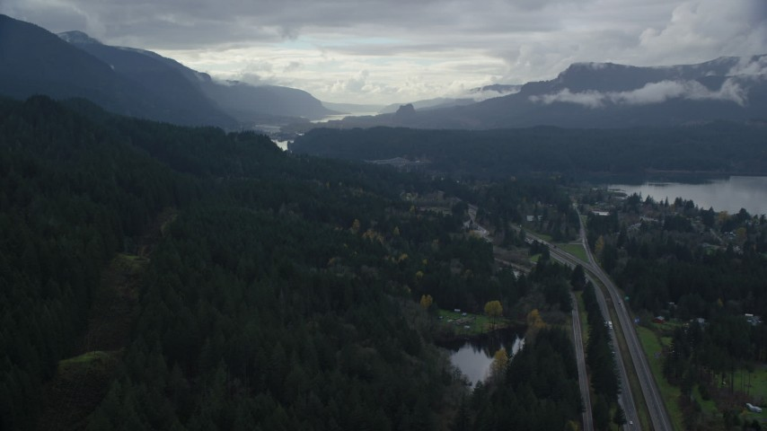 6K stock footage aerial video flying over forest by Interstate 84, Cascade Locks, Oregon in Columbia River Gorge Aerial Stock Footage | AX154_168