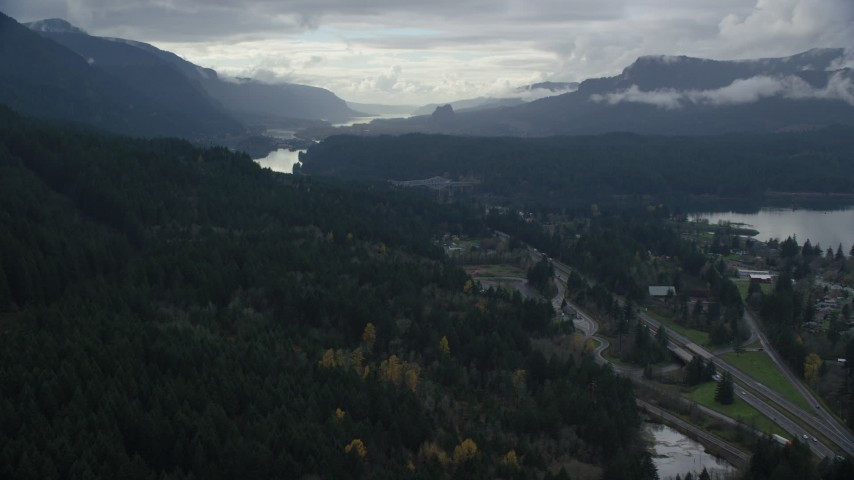 6K aerial video flying over forest by Interstate 84 to approach Bridge of the Gods, Cascade Locks, Oregon in Columbia River Gorge Aerial Stock Footage | AX154_169