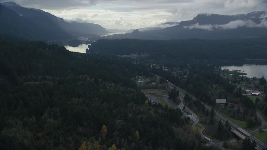 6K stock footage aerial video flying over forest by Interstate 84 to approach Bridge of the Gods, Cascade Locks, Oregon in Columbia River Gorge Aerial Stock Footage | AX154_169