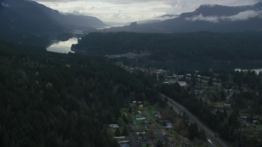 6K stock footage aerial video flying over evergreens by Interstate 84 to approach the Bridge of the Gods, Cascade Locks, Oregon in Columbia River Gorge Aerial Stock Footage | AX154_170