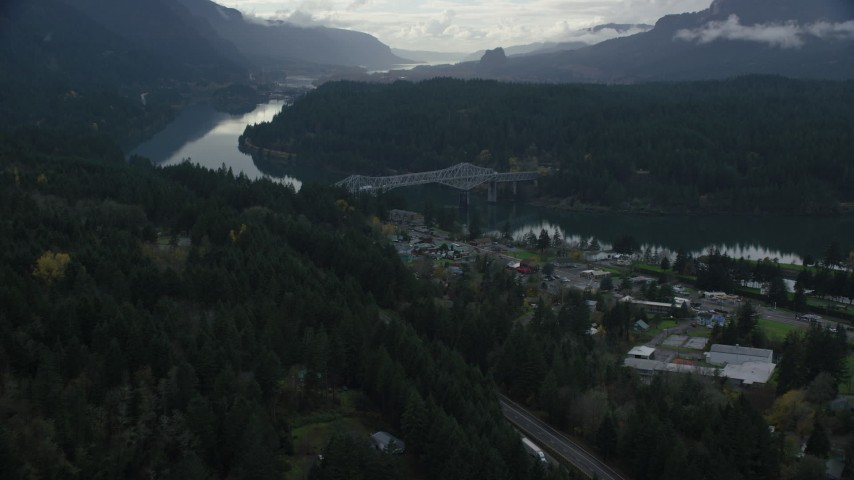 6K stock footage aerial video flying over Interstate 84 and small town RV park to approach the Bridge of the Gods, Cascade Locks, Oregon in Columbia River Gorge Aerial Stock Footage | AX154_171
