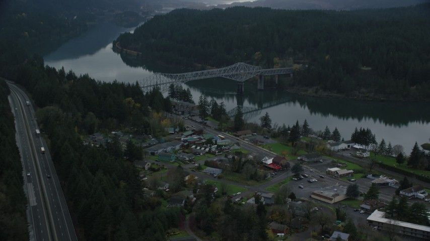 6K stock footage aerial video flying over Interstate 84 and small town RV park to approach the Bridge of the Gods, Cascade Locks, Oregon in Columbia River Gorge Aerial Stock Footage   AX154_171