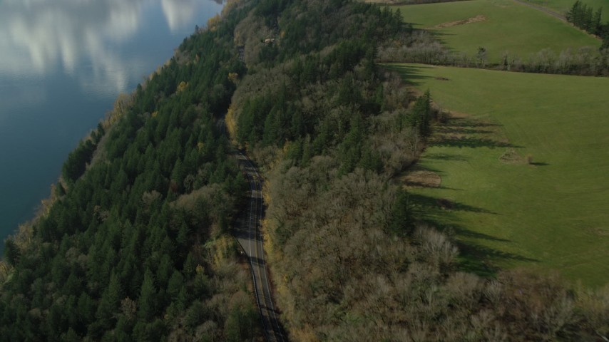 6K stock footage aerial video of a bird's eye view of Highway 14 through forest, tilt to reveal an isolate home and green fields, Washougal, Washington Aerial Stock Footage | AX154_197