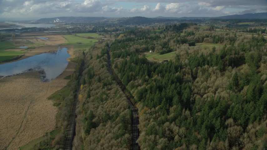 6K stock footage aerial video flying over railroad tracks and Highway 14 through forest in Washougal, Washington Aerial Stock Footage | AX154_199