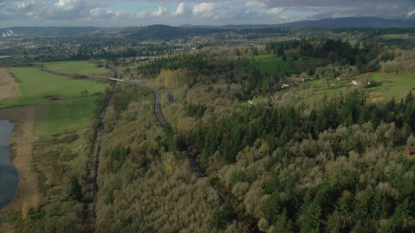6K stock footage aerial video flying over railroad tracks and Highway 14 beside forest near rural homes in Washougal, Washington Aerial Stock Footage | AX154_200