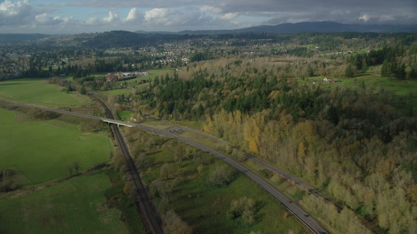 6K stock footage aerial video flying over railroad tracks and Highway 14 beside forest near rural homes in Washougal, Washington Aerial Stock Footage | AX154_201