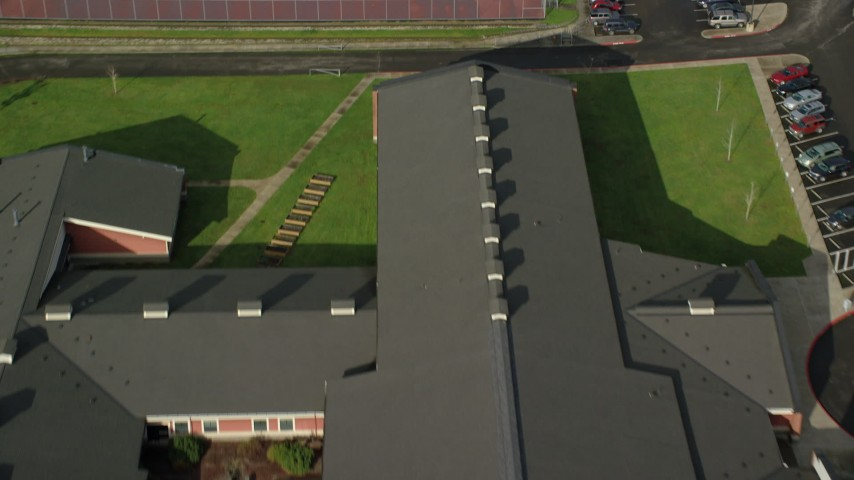 6K stock footage aerial video tilting from the roof of Washougal High School to reveal suburban neighborhoods in Washougal, Washington Aerial Stock Footage | AX154_203