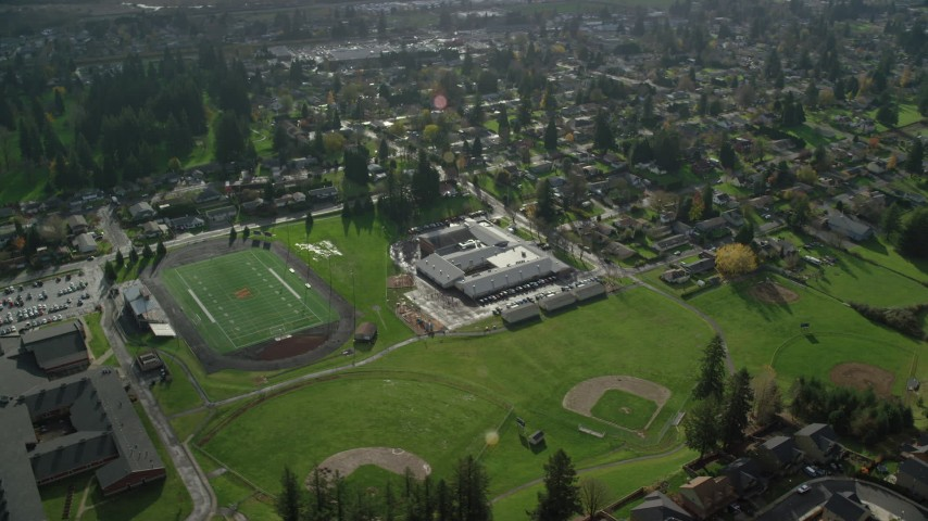 6K stock footage aerial video orbiting Gause Elementary, Washougal High School, sports fields, and suburban houses in Washougal, Washington Aerial Stock Footage | AX154_208
