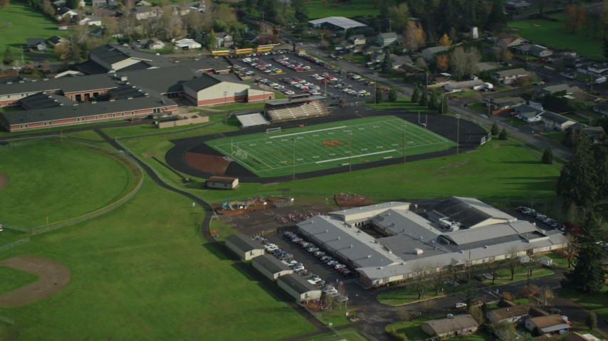 6K stock footage aerial video flying away from Gause Elementary, Washougal High School, and sports fields in Washougal, Washington Aerial Stock Footage | AX154_209