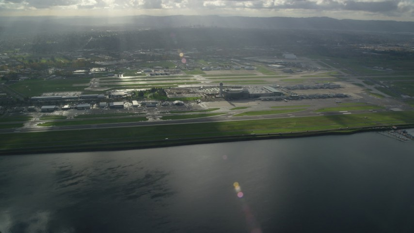 6K stock footage aerial video of godrays shining down on the Portland International Airport, approach from the Columbia River Aerial Stock Footage | AX154_220